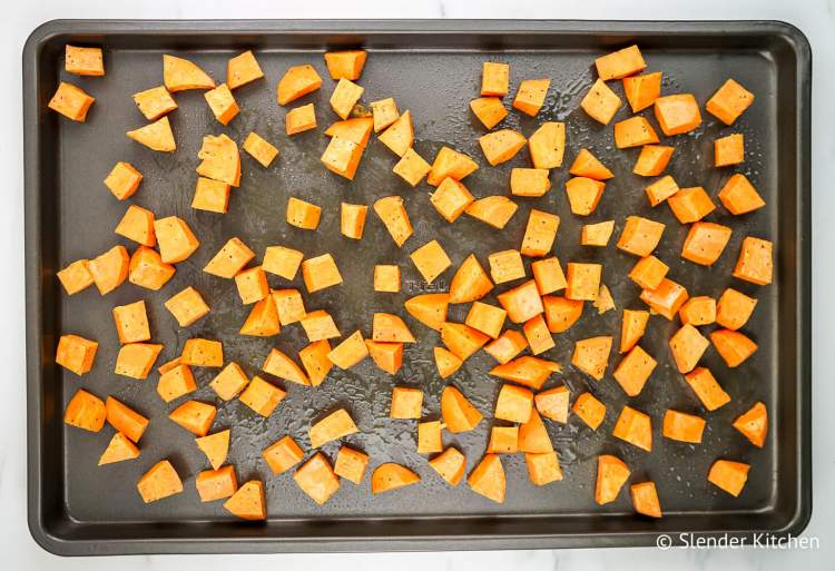 Sweet potatoes on a baking sheet before being roasted with olive oil, salt, and pepper.