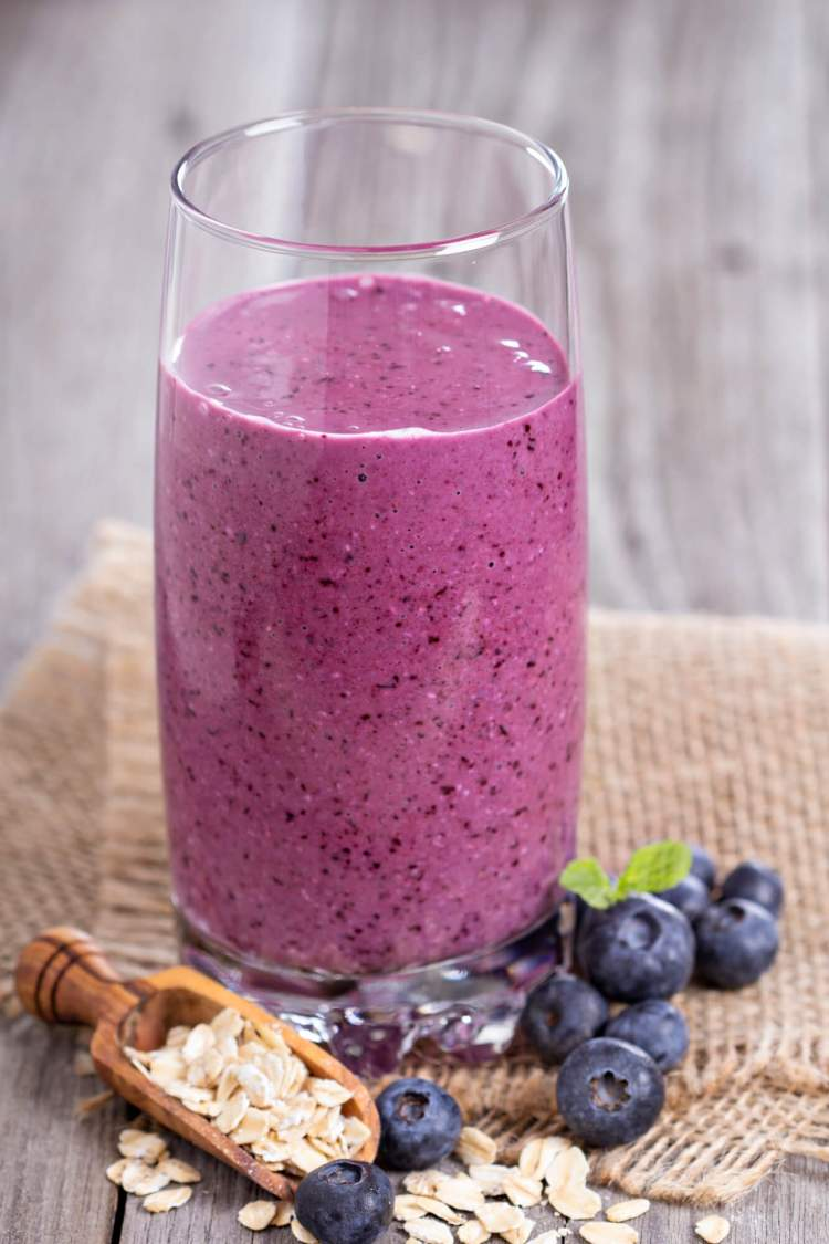 Oatmeal smoothie in a tall glass with blueberries and oats on the side.