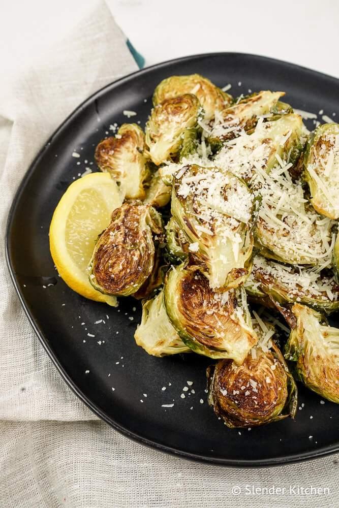 Parmesan Brussels Sprouts with lemon on a black plate.