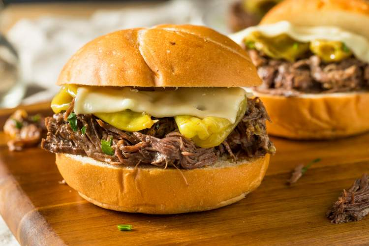 Pepperoncini recipe for beef in a slow cooker served on a sandwich bun with cheese.