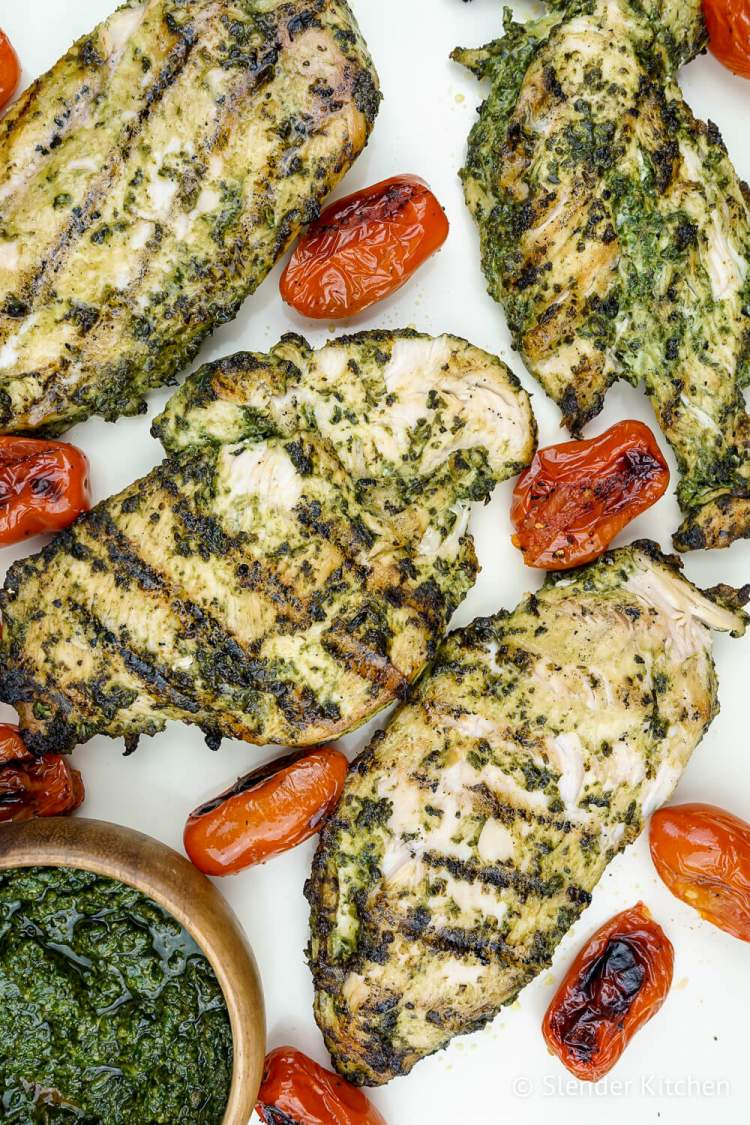 Pesto chicken with cherry tomatoes on a white baking sheet.