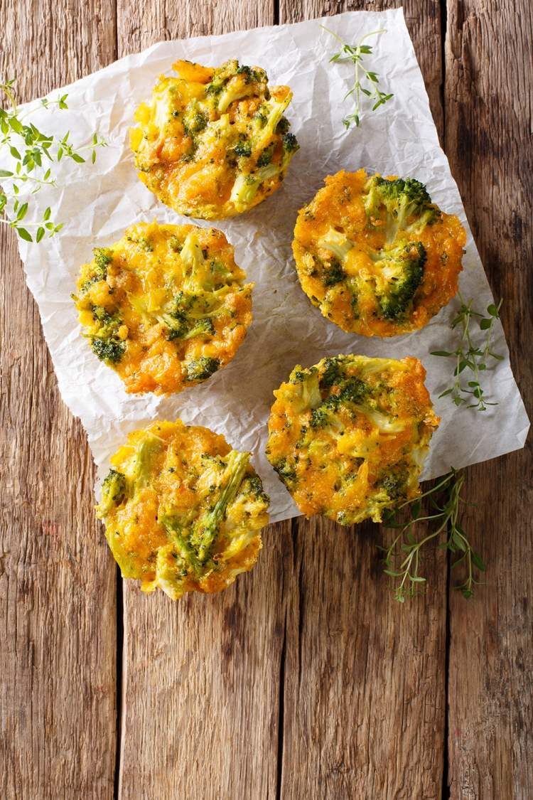 Quiche muffins with turkey and broccoli on parchment paper and a wooden background.