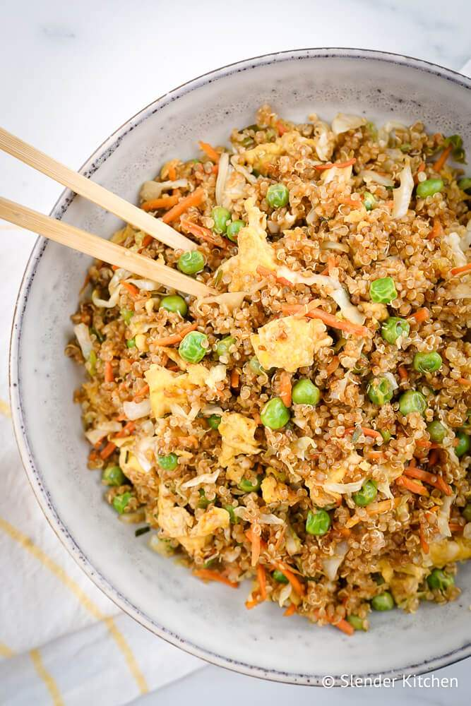 Quinoa fried rice in a bowl with quinoa, vegetables, eggs, and soy sauce.