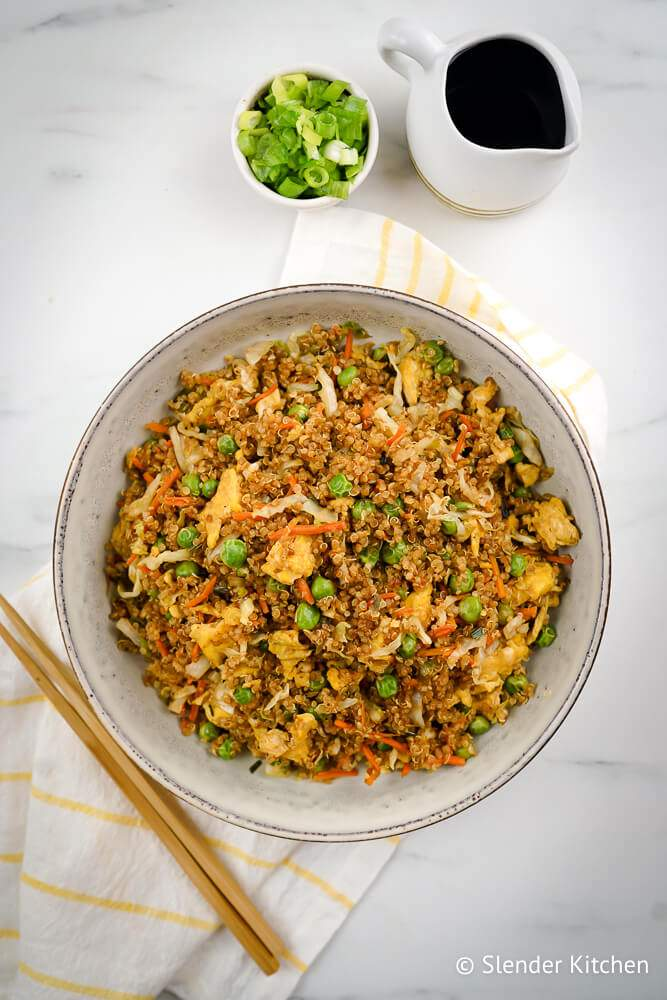 Fried rice with quinoa in a bowl with chopsticks, chopped green onions, cooke quinoa, eggs, and vegetables.