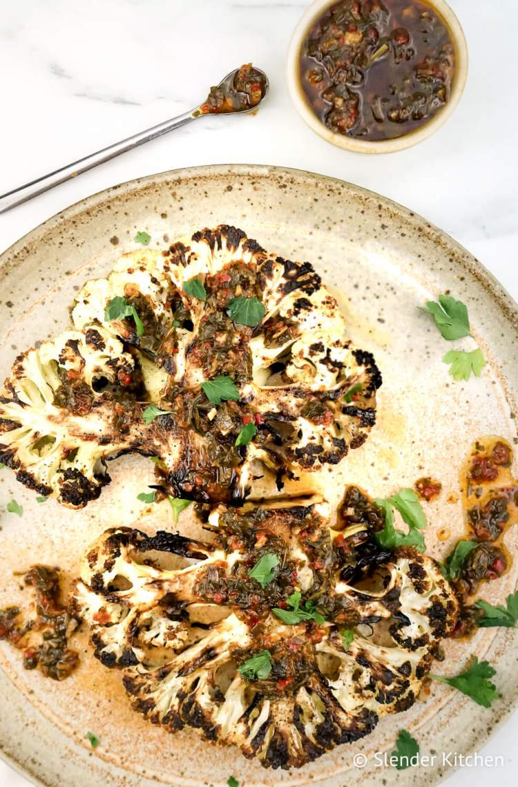 Roasted cauliflower steaks on a clay plate with chimichurri on top and a marble white background.