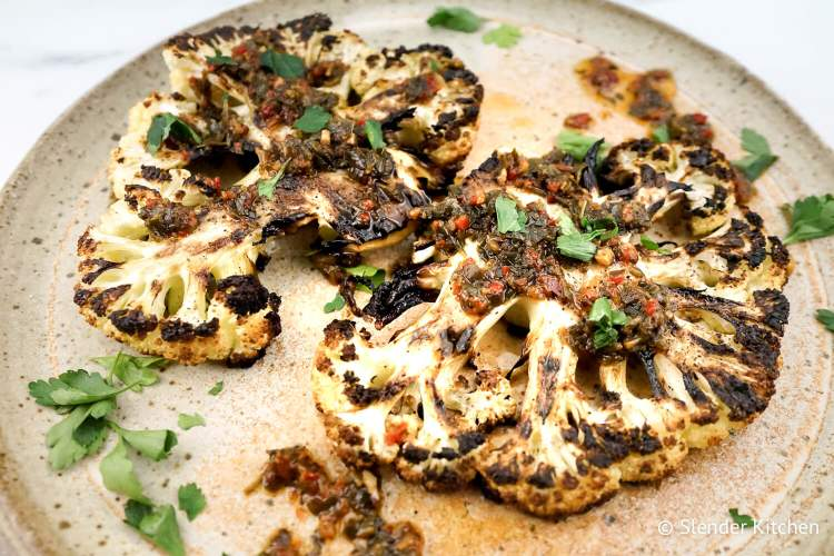 Cauliflower steaks served with chimmichurri on speckled gray plate.