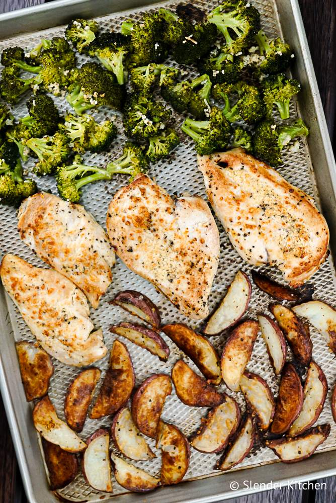 Chicken and potatoes with broccoli on a silver baking sheet with minced garlic.