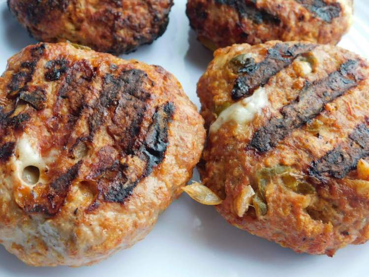 Four turkey burgers stuffed with salsa and cheese that have grill marks.