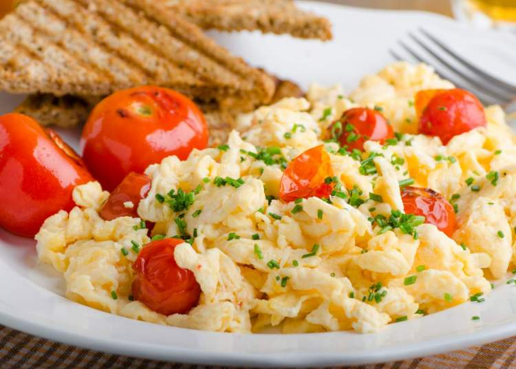 Scrambled Eggs with tomatoes and toast.
