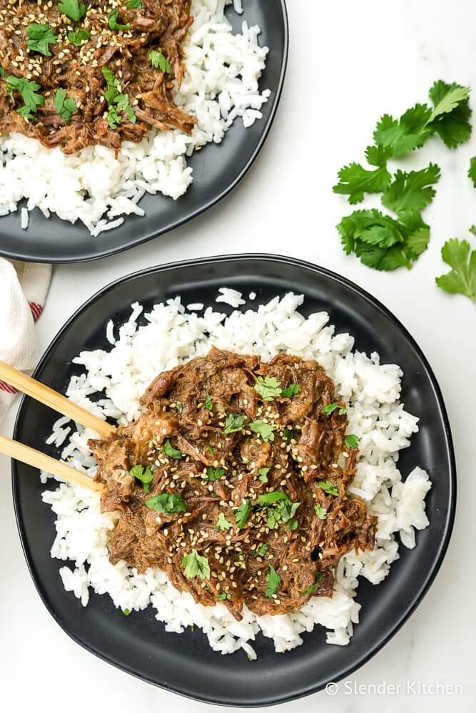 Sesame beef over rice with cilantro and sesame seeds.