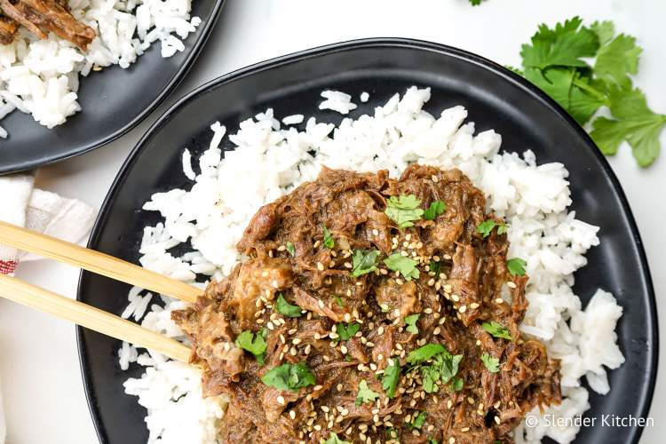 Slow Cooker Sesame Beef  over rice with sesame seeds and chopsticks.