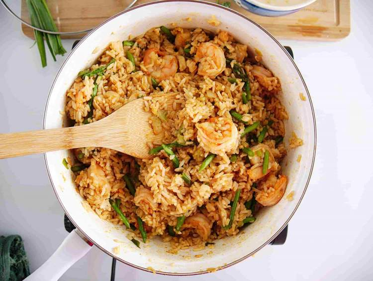 Fried Rice with Shrimp with asparagus, lime, and a wooden spoon.