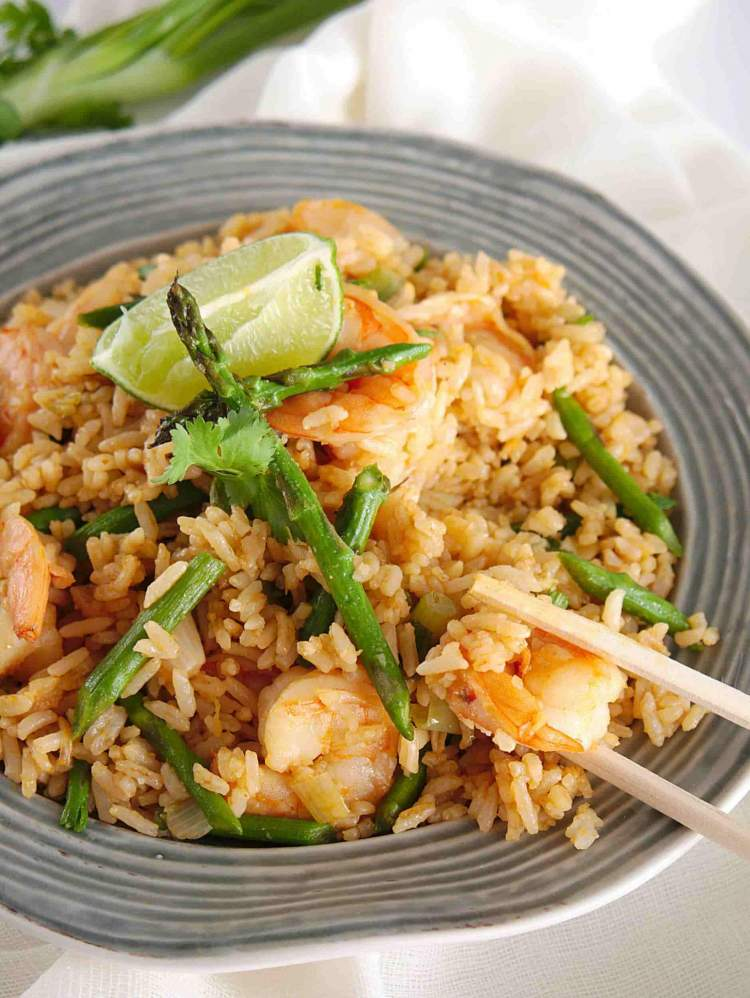 Shrimp fried rice with soy sauce, asparagus, and a lime wedge on a light blue plate.