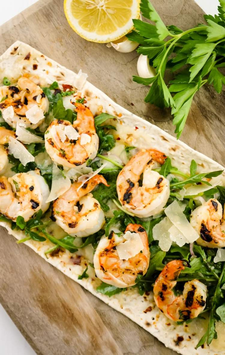 Shrimp Scampi Flatbread ready to be served and cut into slices.