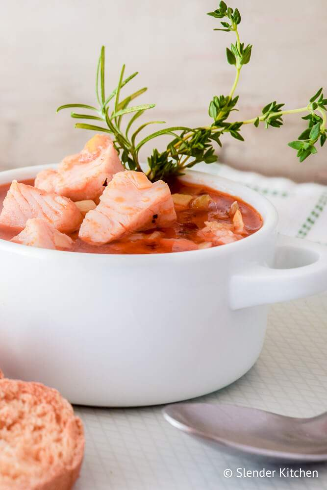 Simple fish stew with carrots, celery, onions, and garlic in a bowl with a napkin on the side.