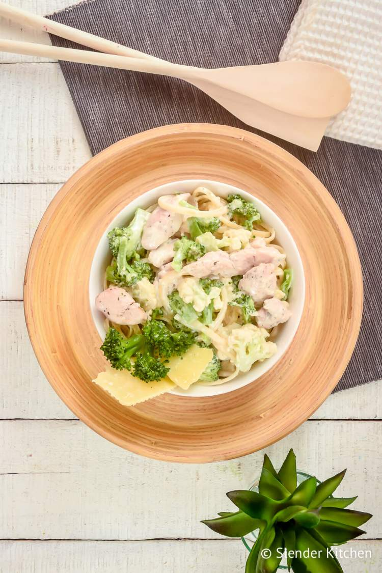 Lightened up chicken broccoli alfredo in a bowl with a wooden plate and wooden utensils.
