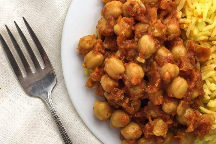 Crockpot chana masala with rice on a white plate with a fork