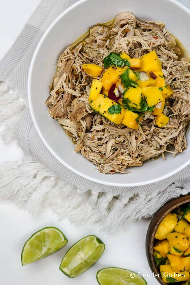 Crockpot jerk chicken shredded in a bowl with lime slices and mango salsa.