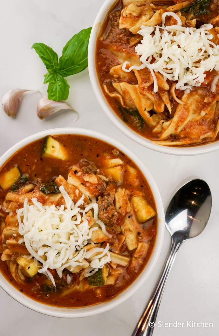 Healthy Slow Cooker Lasagna Soup in a bowl with fresh basil and mozzarella cheese.