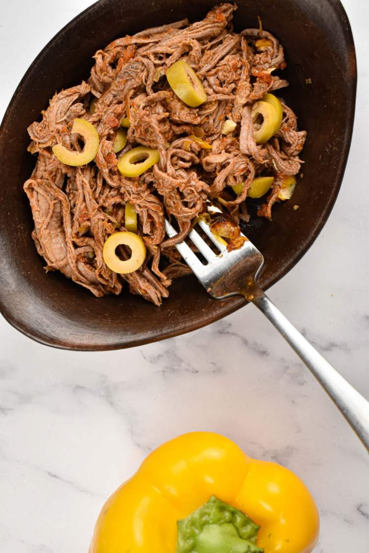 Crockpot ropa vieja in a black dish with shredded beef, peppers, onions, tomatoes, and olives.
