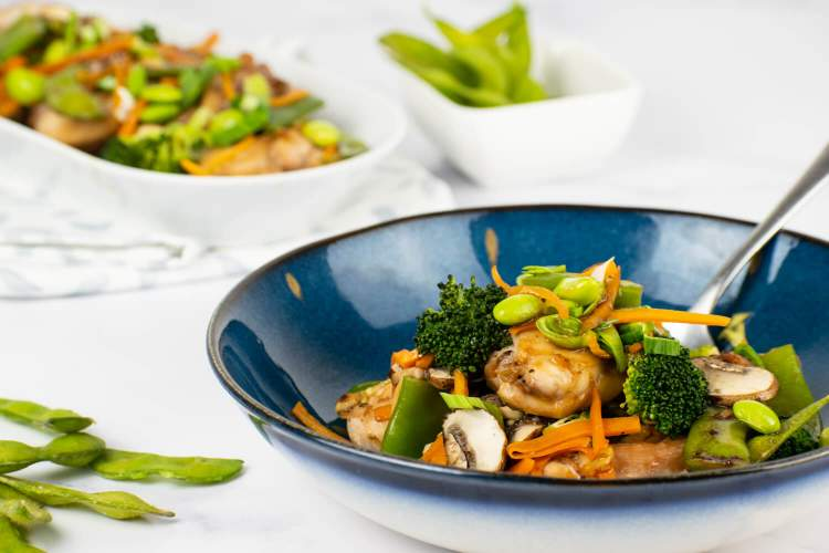 Chicken with soy sauce and vegetables in a bowl with a plate of chicken in the background.