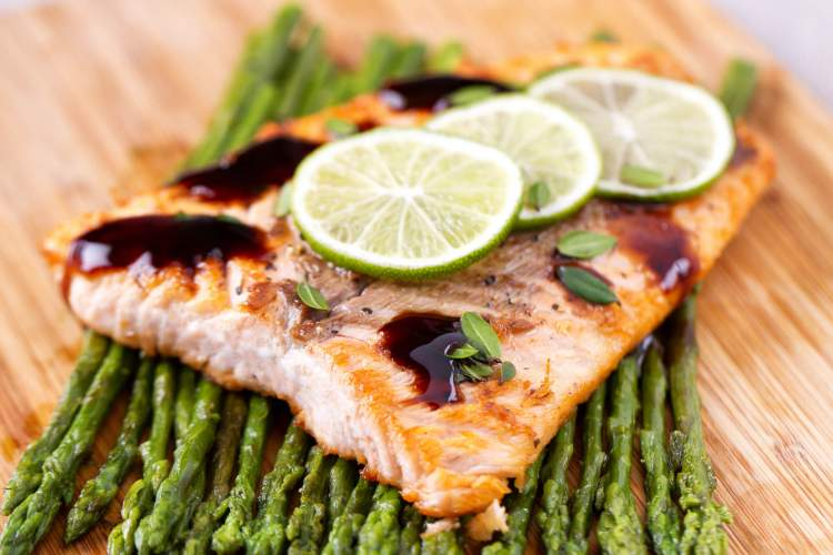 Baked Spicy salmon on a cutting board with asparagus.