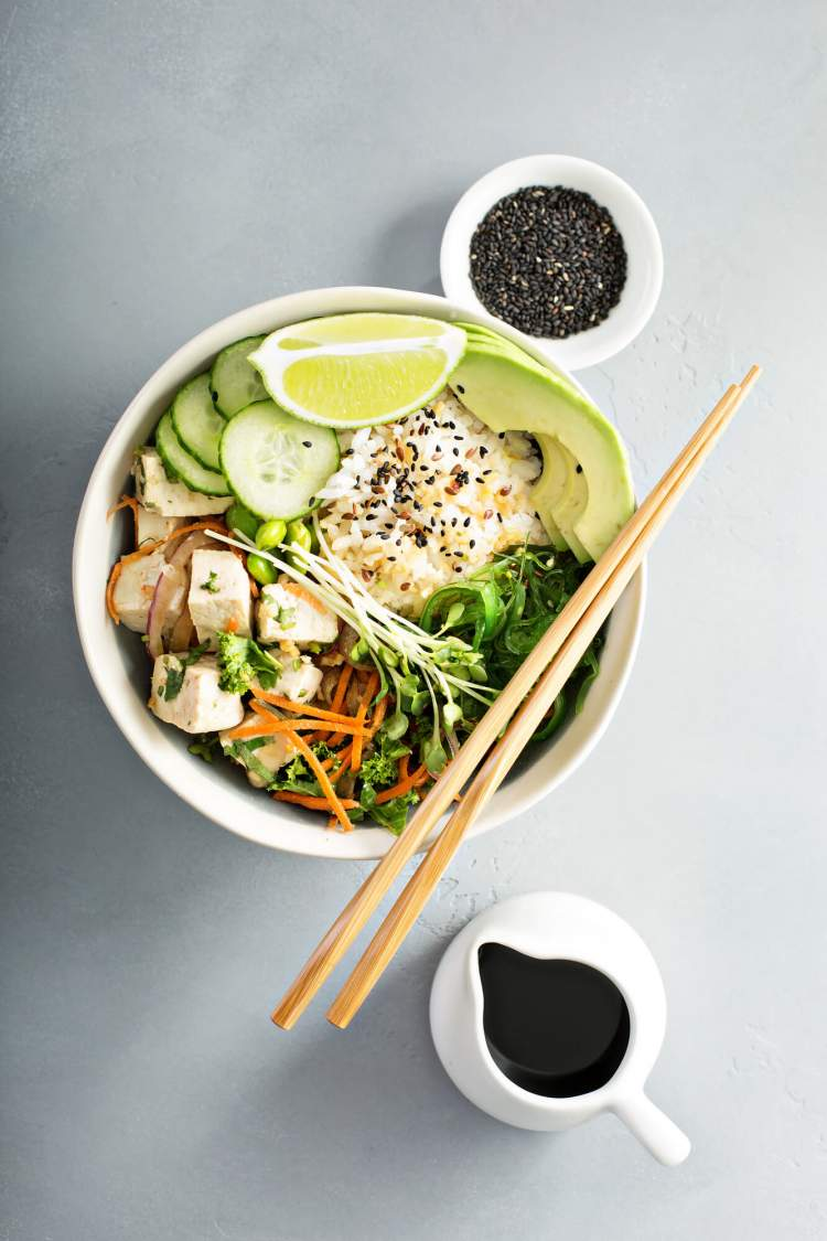 Vegetarian sushi bowl with edamame, pea shoots, avocado, tofu, and sesame seeds.
