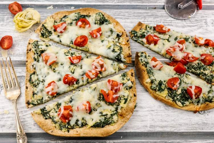 Spinach Artichoke Pizza on a thin flatbread with tomatoes.