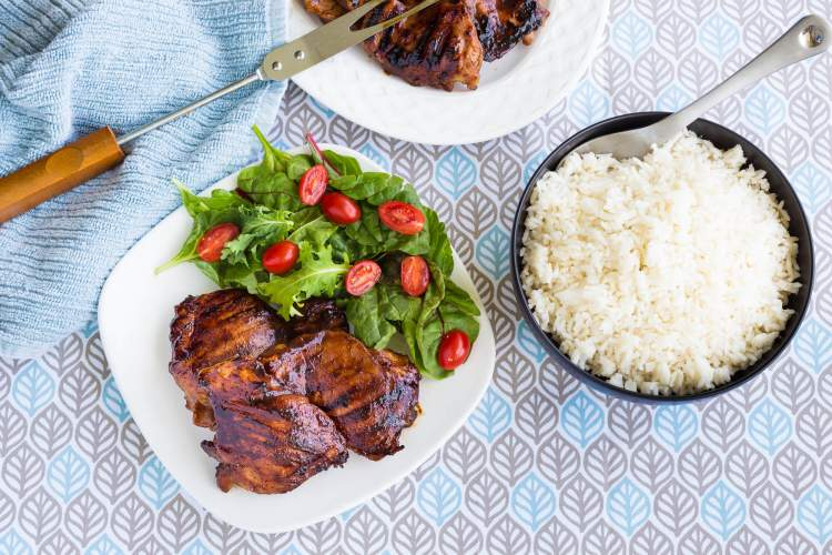 Sriracha recipe for chicken on a plate with salad and a blue napkin.