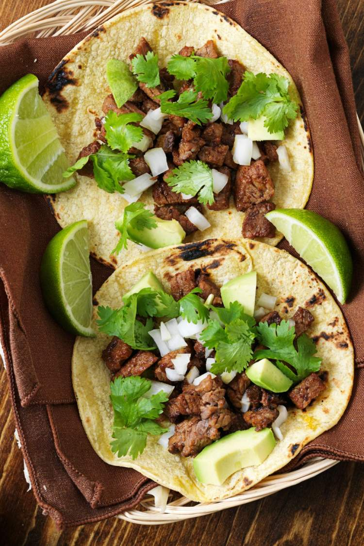 Two grilled steak tacos topped with cilantro and onion in a basket with a brown napkin inside