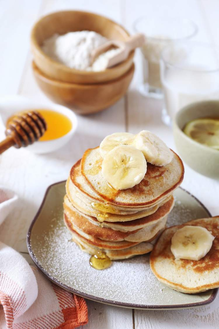 Three Ingredient Banana and Egg Pancakes stacked on a plate with bananas and strawberries