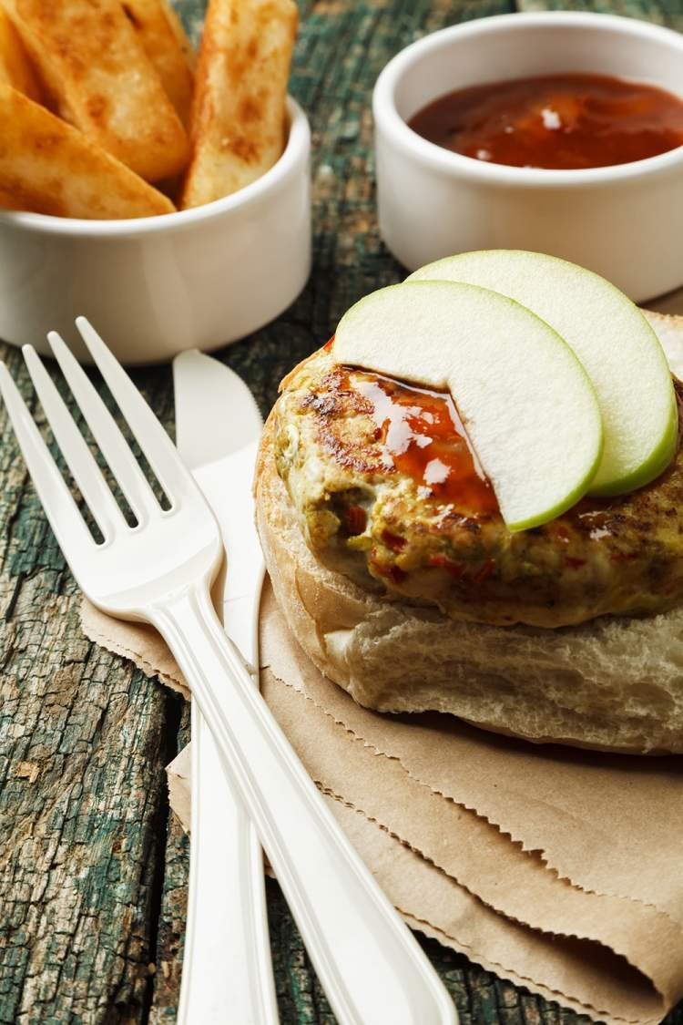 Turkey Apple Burger with thin apple slices and baked french fries.
