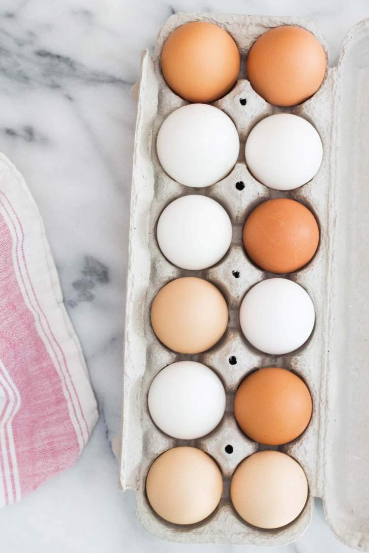Different types of eggs in a carton including white, brown, and tan.