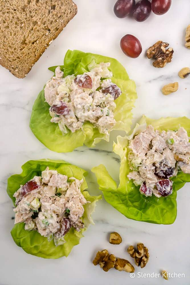 Chicken waldorf salad with grapes, apples, walnuts, and celery in lettuce leaves.
