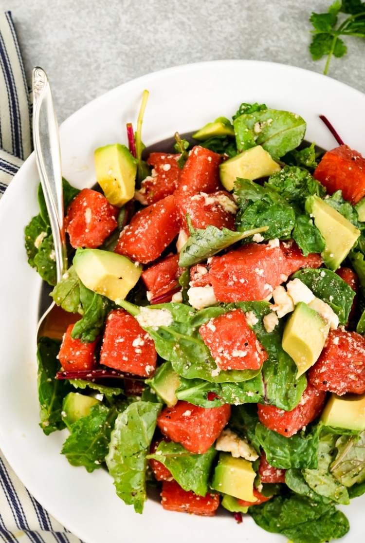 Watermelon and Avocado Salad with Honey Lime Vinaigrette with creamy feta cheese and greens.