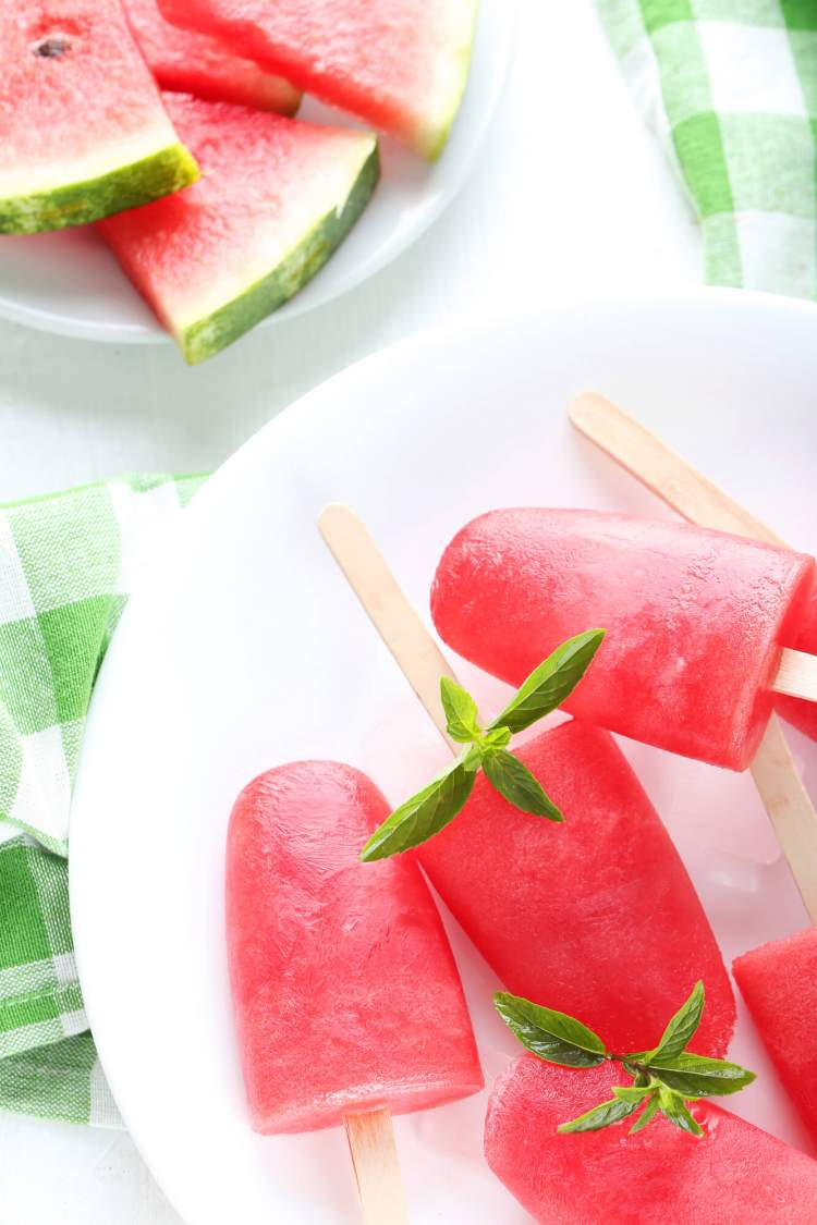Watermelon popsicles and pieces of fresh watermelon on a white counter.