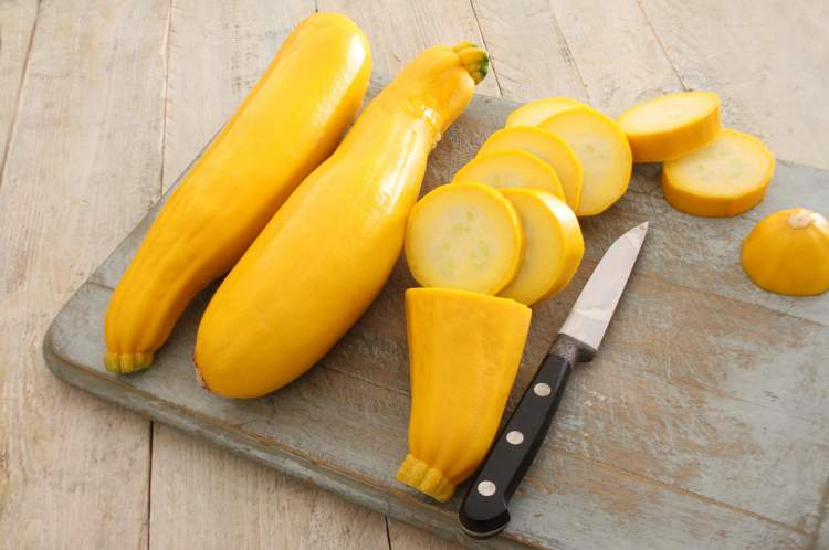 Summer squash on a cutting board with a knife.