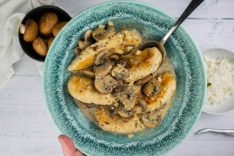 Creamy Garlic Mushroom Chicken in a blue bowl with rice on the side.