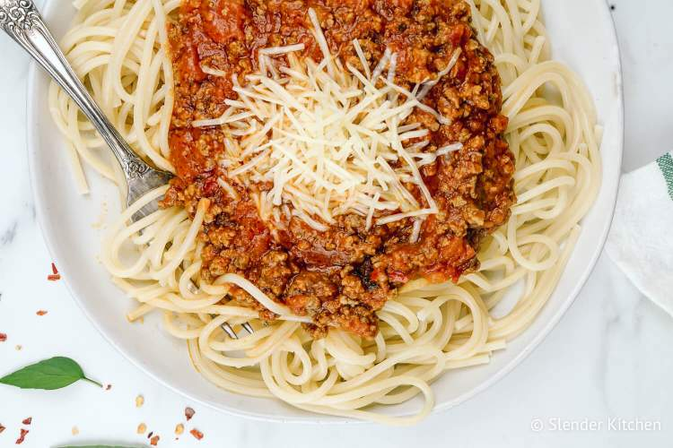 Ground turkey spaghetti arrabiata on a bed of pasta with a fork and napkin.