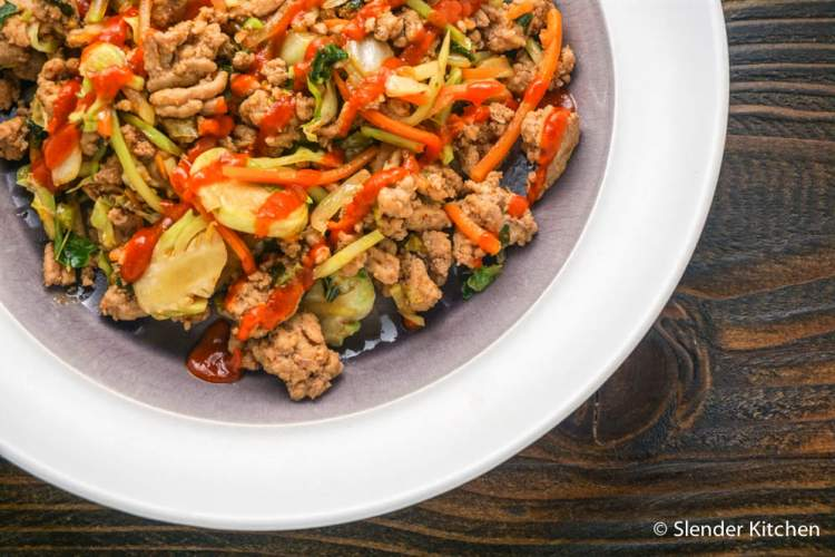 Ground turkey and vegetable stir fry with Sriracha on top.