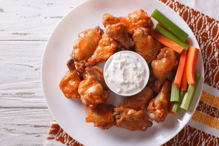 Baked buffalo wings on a plate with celery, carrots, and ranch dressing.