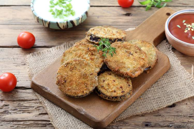 Baked eggplant cutlets on a wooden cutting board with tomatoes and herbs.