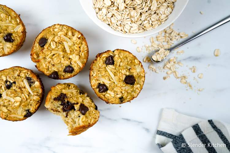 Banana Coconut Chocolate Oatmeal Muffins with loose oats on a marble board.