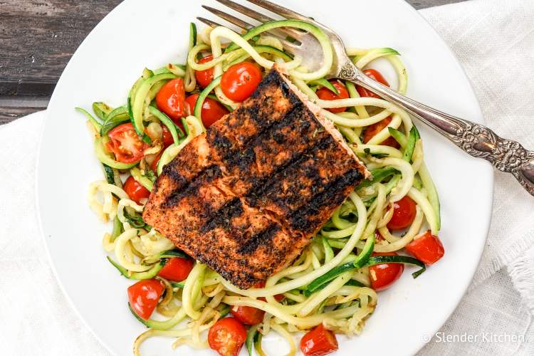 Zoodles on a white plate with salmon and tomatoes.