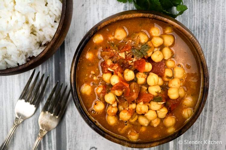 Chana masala with tomatoes and chickpeas with a bowl of white rice and forks.