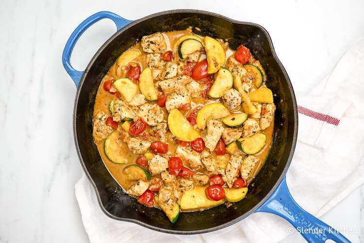 Creamy tuscan chicken with zucchini, summer squash, and tomatoes in a cast iron skillet.
