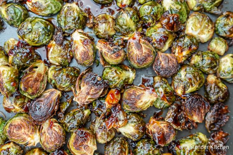 Roasted Brussel sprouts on a sheet pan with an Asian sauce.