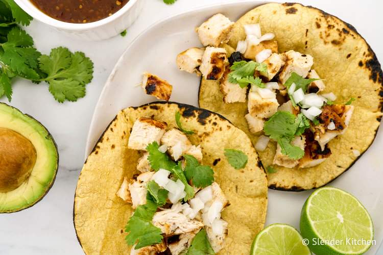 Grilled Chicken Tacos on tortillas with lime and onion.