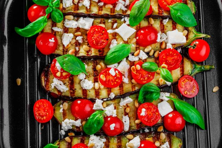Grilled eggplant recipe on a grill pan with tomatoes and cheese.