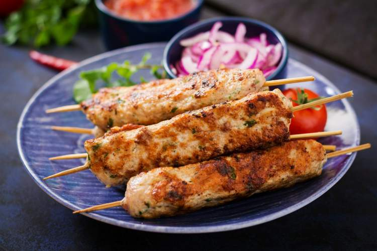Ground turkey lula kabobs on a plate with parsley and onions in the background.